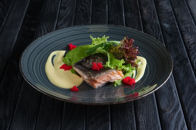 Fried piece of salmon with creamy sauce and green salad leaves decorated with caviar