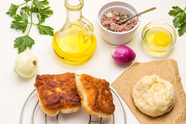 Жареные пироги на металлической подставке под горячее. бумага, сырое тесто. мясной фарш и вилка на миске. бутылка оливкового масла. белый фон. вид сверху