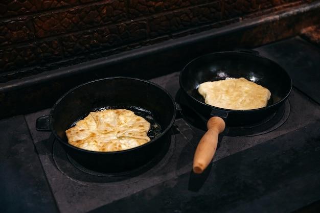 Жареные пирожки с творогом в чугунных сковородках на деревенской печи
