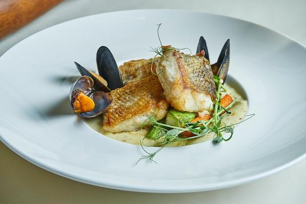 Жареное филе судака со сливочным соусом и мидиями в белой миске. в ресторане подают блюда. морепродукты на обед