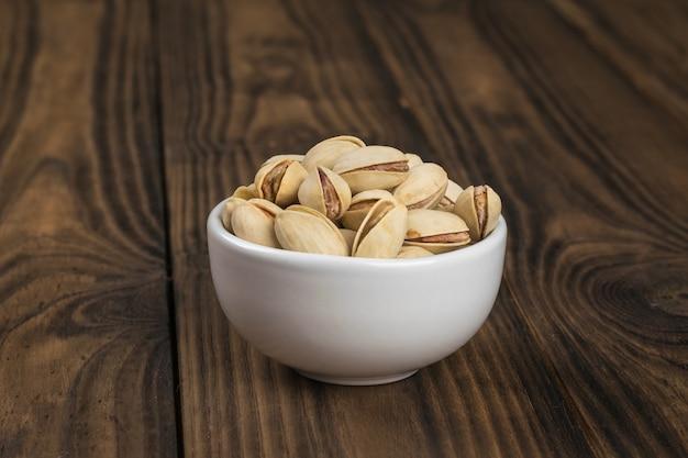 나무 테이블에 흰색 도자기 컵에 튀긴 피스타치오. 단백질과 탄수화물의 천연 공급원.
