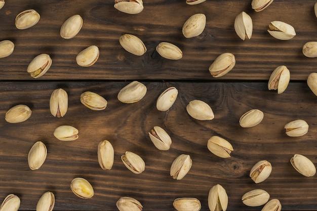 튀긴 피스타치오가 나무 테이블에 흩어져 있습니다. 단백질과 탄수화물의 천연 공급원입니다.