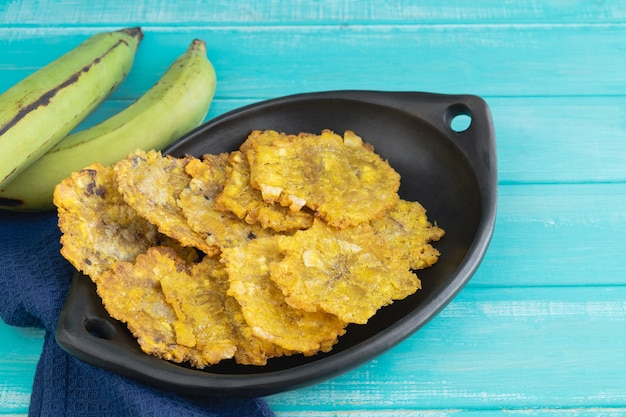 Fried plantain. patacones on black plate on blue background. copy space.