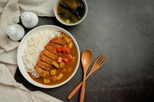 Cotoletta di maiale fritta al curry con riso sulla superficie scura