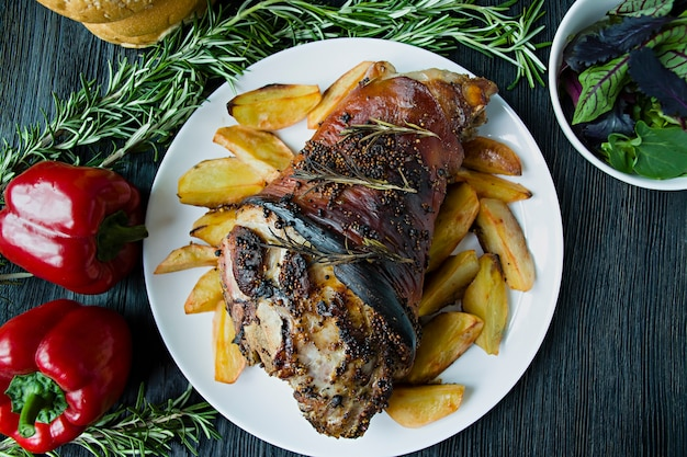 Fried pork knuckle with potatoes served on a white plate