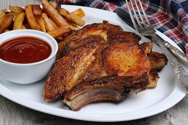 Жареный стейк из свиной корейки с картофелем фри и томатным соусом