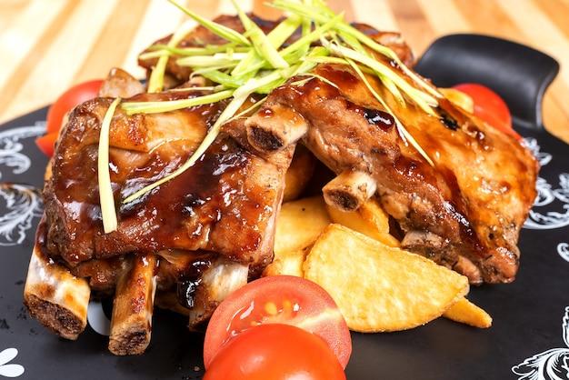 Жареные свиные ребрышки с картофелем и зеленью. для любых целей.