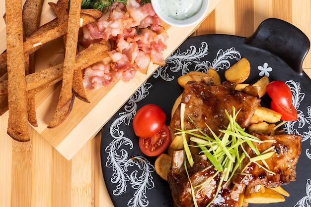 Жареные свиные ребрышки с картофелем и зеленью. с порцией крекеров. для любых целей.