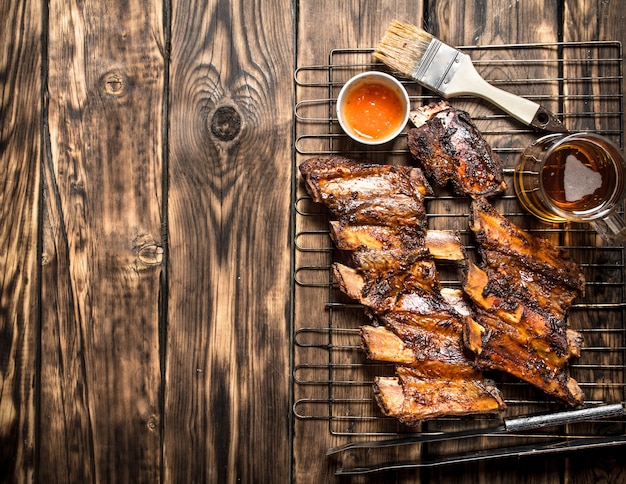 Жареные свиные ребрышки с томатным соусом на деревянном столе