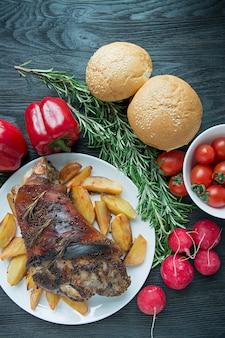 ポテトの炒めたシャンクに白いプレートを添えて焼き豚肉。ダークウッド。上からの眺め。