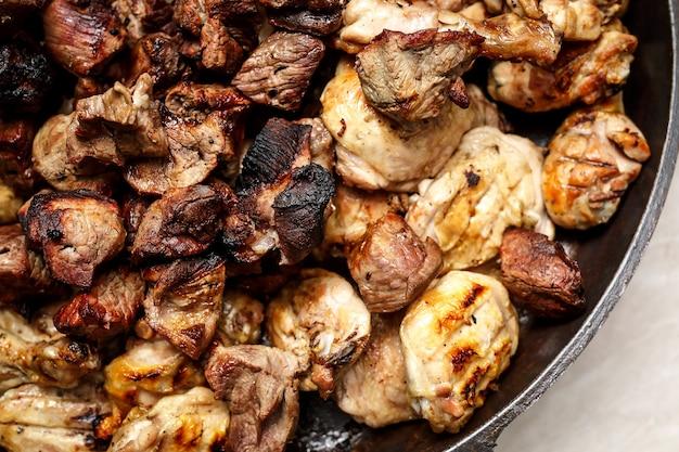 Жареный стейк из свинины в сковороде, вид крупным планом.