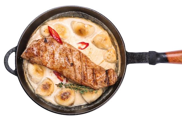 흰색 배경에 고립 된 흰색 souce와 프라이팬에 튀긴 돼지 고기 스테이크. 맛있는 스테이크, 수스에 흰 버섯.