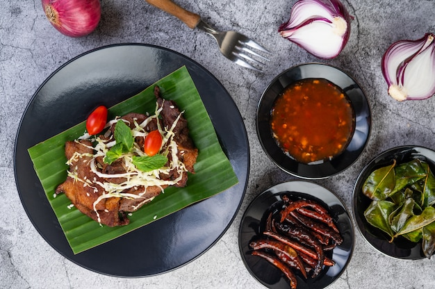 Fried pork topped with sesame seeds put on a banana leaf in a black dish.