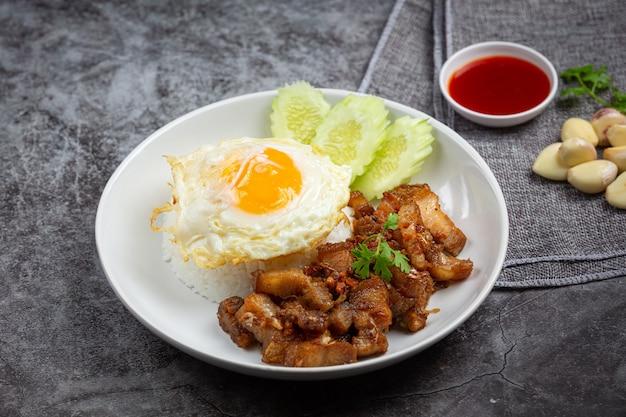 にんにくと胡椒を添えた豚肉の炒め物にご飯と目玉焼きを添えて