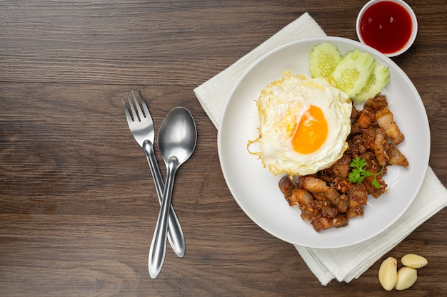 Жареная свинина с чесноком и перцем, подается с рисом и жареным яйцом