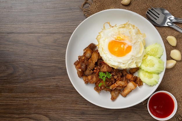 Fried pork with garlic and pepper served with rice and fried egg