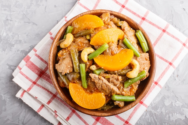 Fried pork with peaches, cashew and green beans in a wooden bowl, close up, top view.
