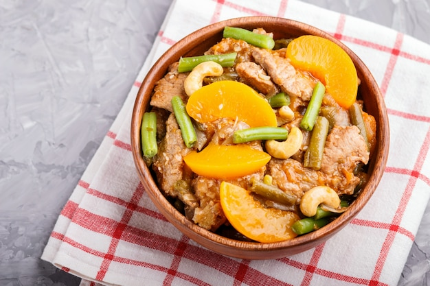 Fried pork with peaches, cashew and green beans in a wooden bowl on gray