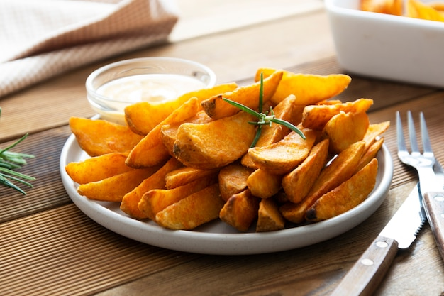 Fried potato chips with herbs and sauce in white plate, golden roasted potatoe slices with herbs.