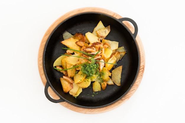 Картофель жареный, заправленный зеленью. полная сковорода на подносе.