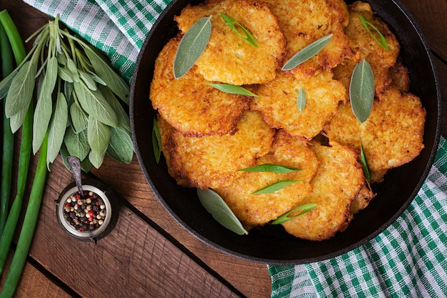 Fried potato pancakes in a frying pan on a wooden table.