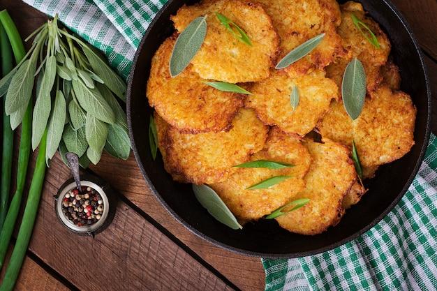 Жареные картофельные оладьи на сковороде на деревянном столе