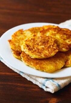 Жареные картофельные оладьи на белой тарелке.