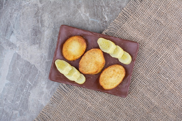 Fried potato slices and pickled cucumbers on plate. high quality photo