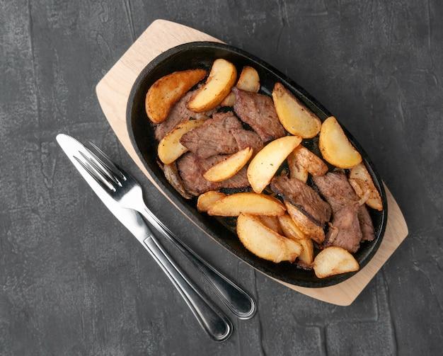 양파와 쇠고기를 곁들인 튀긴 감자 조각. 나무 받침대가 있는 주철 팬에. 팬 옆에는 나이프와 포크가 있습니다. 위에서 볼. 회색 콘크리트 배경입니다.