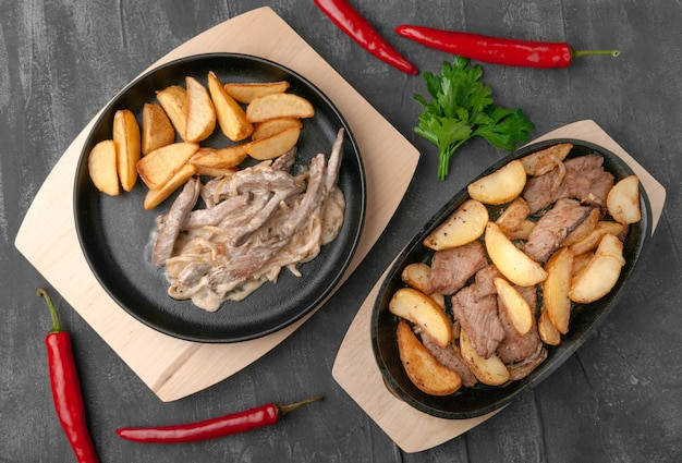 Fried potato slices with onions, beef and beef stroganoff. in a cast-iron pan with a wooden stand. decorated with chili peppers and parsley. view from above. gray concrete background.