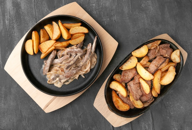 Fried potato slices with onions, beef and beef stroganoff. in a cast-iron pan with a wooden stand. view from above. gray concrete background.