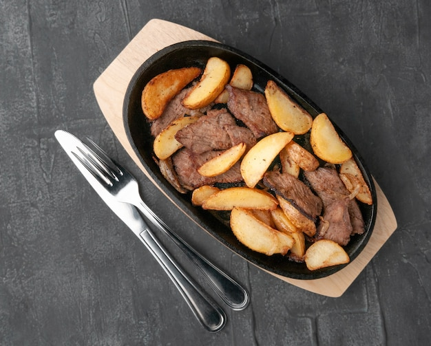 Fried potato slices with onions and beef. in a cast-iron pan with a wooden stand. next to the pan is a knife and a fork. view from above. gray concrete background.