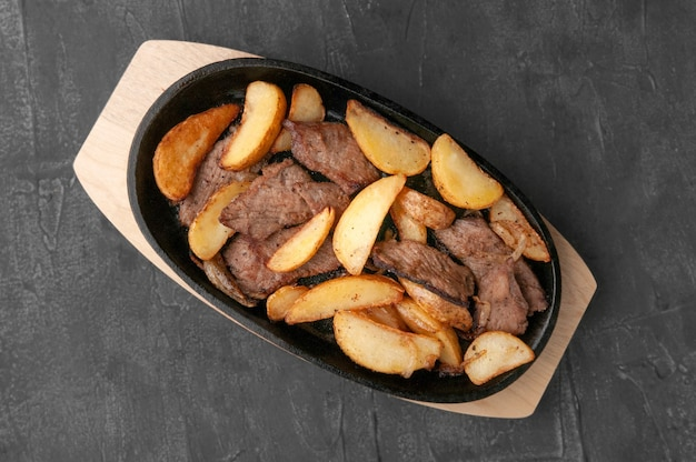 Fried potato slices with onions and beef. in a cast-iron pan with a wooden stand. view from above. gray concrete background.