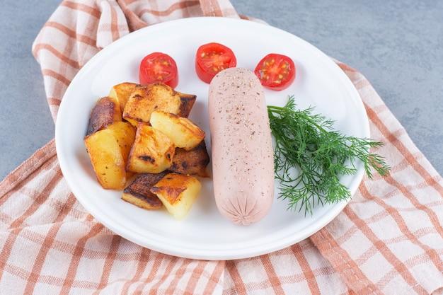 Patate fritte e salsiccia piccante sul piatto bianco.