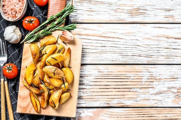 튀긴 감자 웨지, 나무 커팅 보드에 감자 튀김.