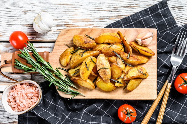 Fried potato wedges, french fries on a wooden cutting board. white background. top view