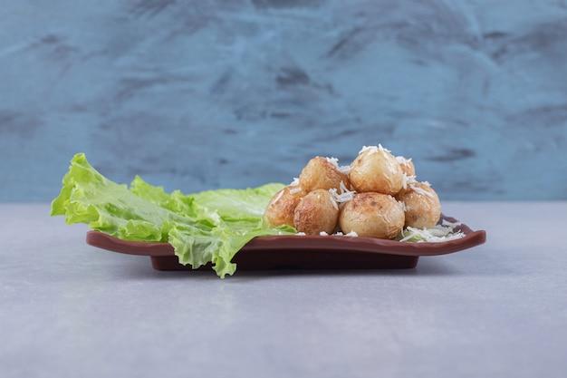 Жареный картофель и салат на коричневой тарелке.
