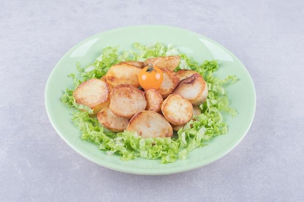 튀긴 감자와 양상추 녹색 접시에.