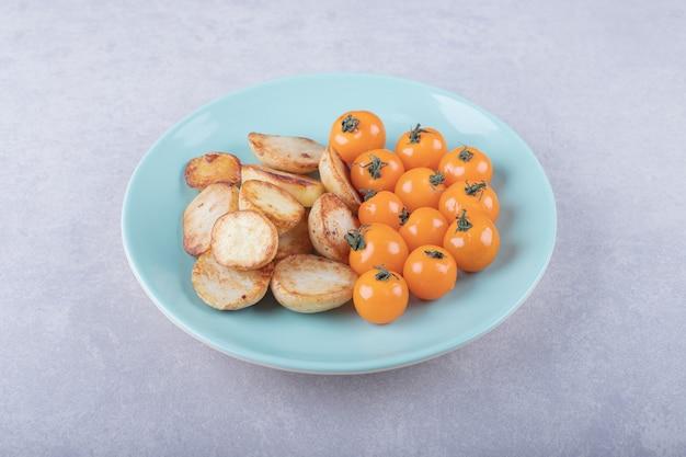 青い皿にフライド ポテトとトマト。