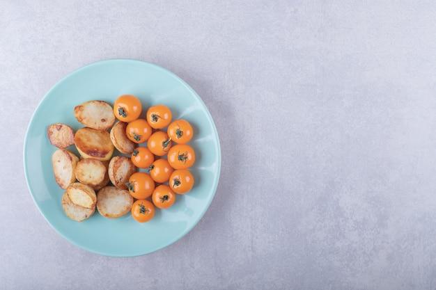 Patate fritte e pomodorini sul piatto blu.
