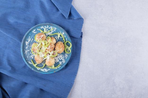 青いプレートにチーズとコショウで飾られたフライドポテト。