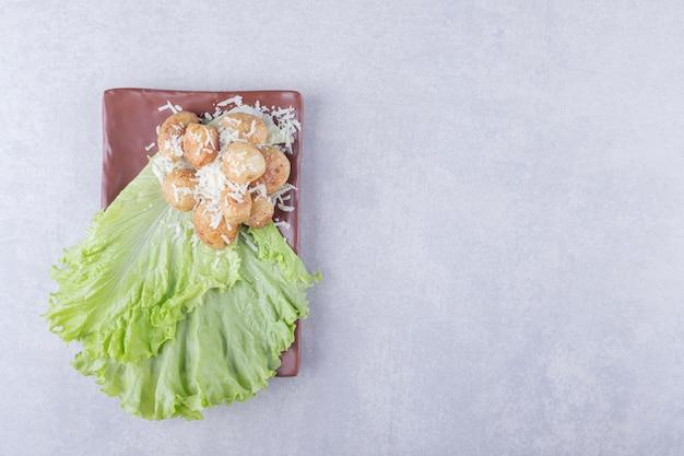 Patate fritte decorate con formaggio su piatto marrone.