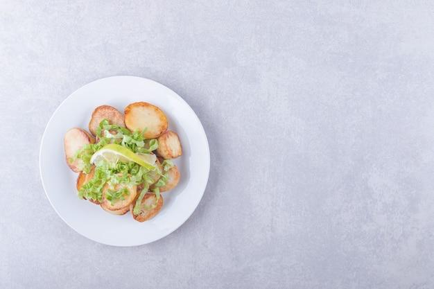Patate fritte decorate con limone e lattuga su piatto bianco.