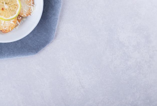 白い皿に粉チーズとレモンを添えたフライドポテト。