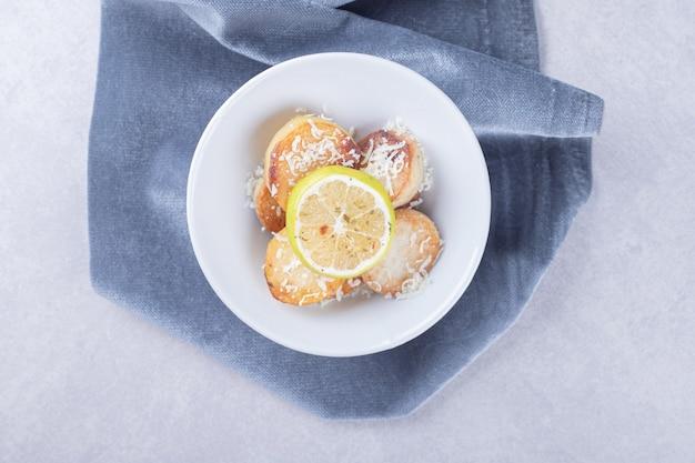 Patate fritte guarnite con formaggio grattugiato e limone sul piatto bianco.
