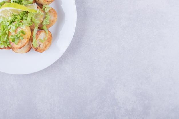 白い皿にレモンを添えたフライドポテト。