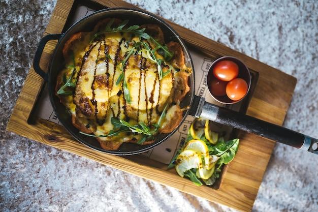 Жареный картофель на сковороде с помидорами на деревянной подставке.