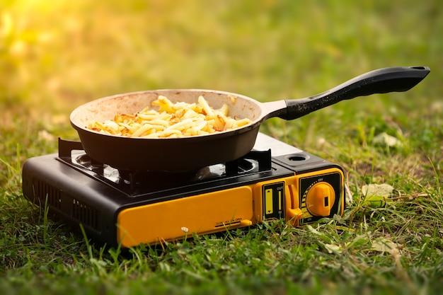 Жареный картофель на сковороде, приготовленный на газовой плите на пикнике на природе