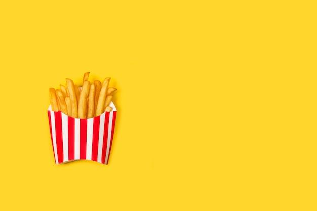 노란색 배경에 줄무늬 빨간색과 흰색 상자에 튀긴 감자