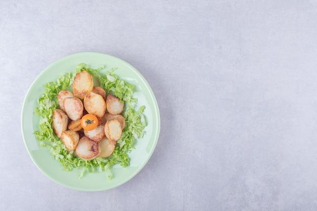 Patate fritte e lattuga sul piatto verde.